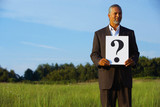 Senior African American businessman holding question mark in field